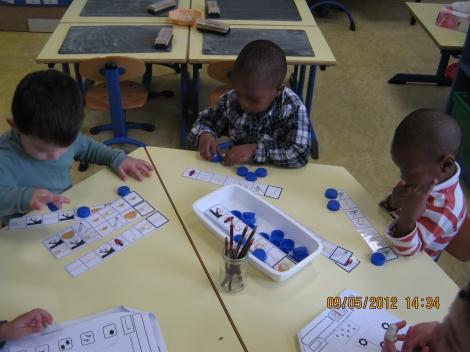 Des élèves retrouvent les mêmes images sur une bande et posent des bouchons dessus.