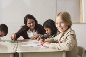 Une enseignante aident ses élèves à réaliser des dessins dans une classe. Les enfants sont souriants et assidus.